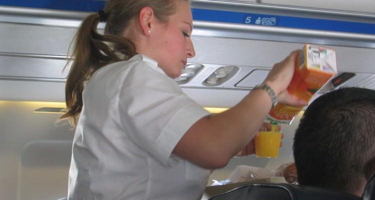 1024px-Stewardess_filling_orangejuice